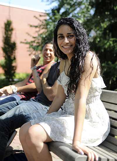 Female student smiles at camera at Adelphi while sitting on bench